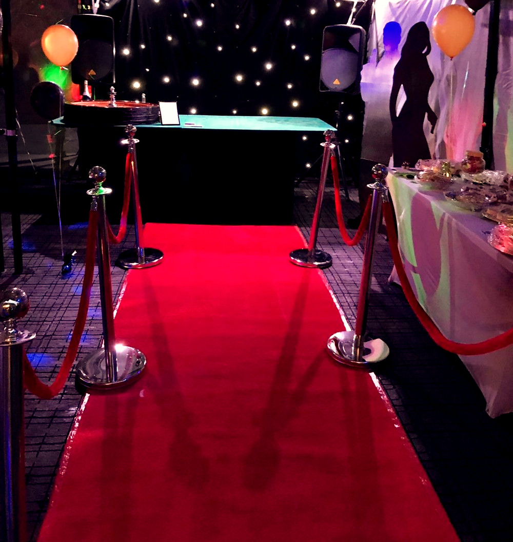 Green roulette table with red carpet and stanchions at a party with a starlit background