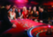 Red Roulett table With motion blur spinning roulette wheel.1 croupier and 7 smiling roulette players at a fun casino party