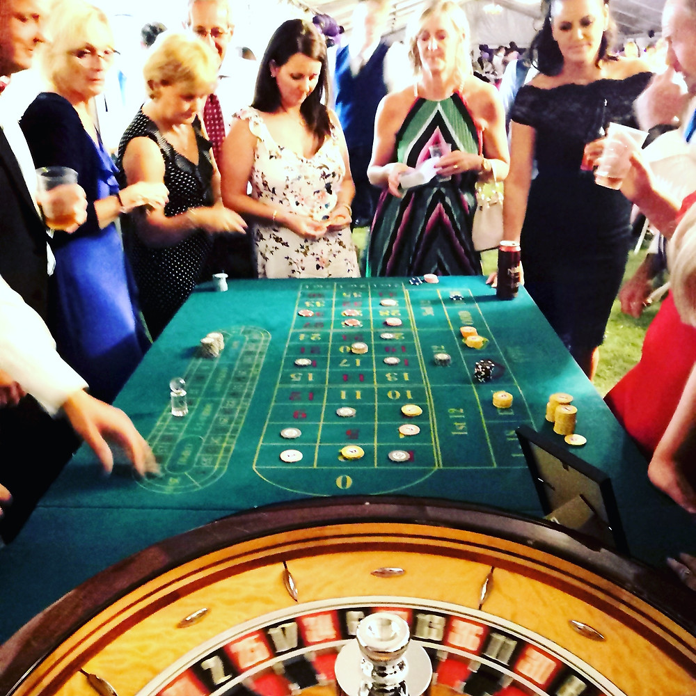 ladies playing roulette at a charity fundraiser. roulette wheel spinning. chips on the roulette table