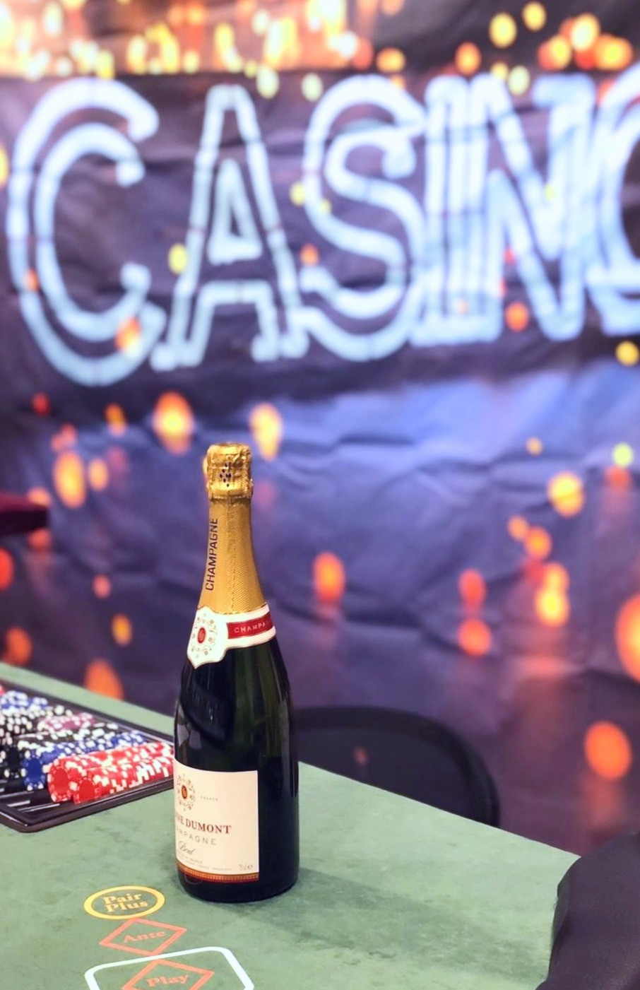 bottle of champagne on a casino table. neon casino background