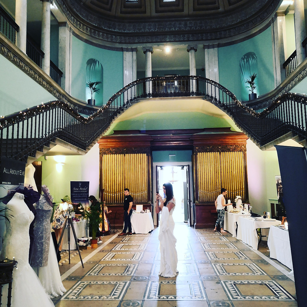 Double staircase leading to the great hall at leigh court. bridal dresses on display and wedding suppliers have tables set up.