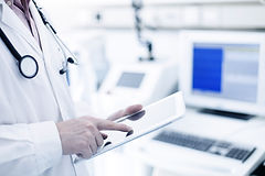 Doctor in white coat uses tablet