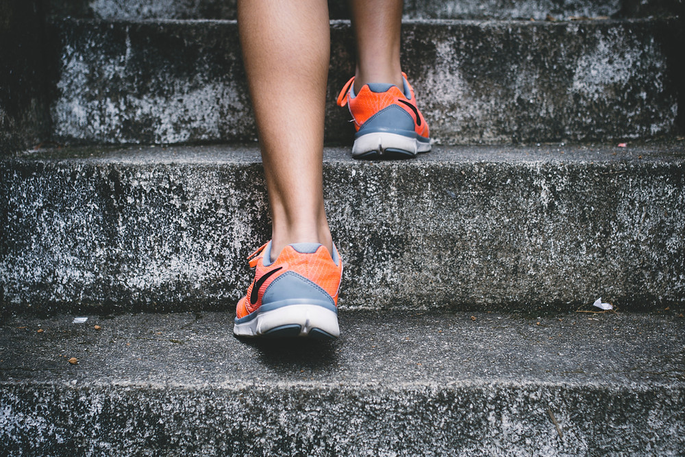 Picture of a person's feet going up steps the trainers are grey and orange