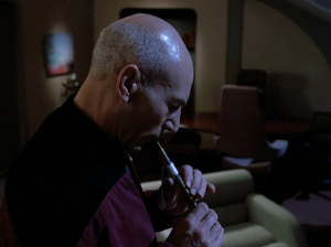 Captain Jean-Luc Picard plays a flute in his quarters, holding the only real relic that remains of his lost life in The Inner Light.