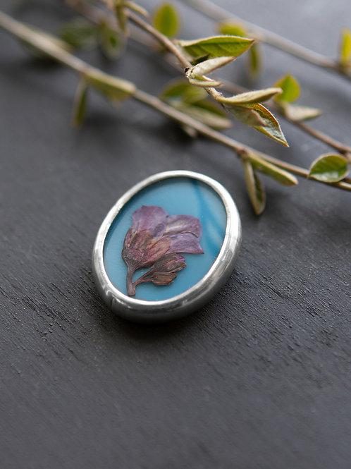 Брошь с фиолетовым цветком на голубом стекле.