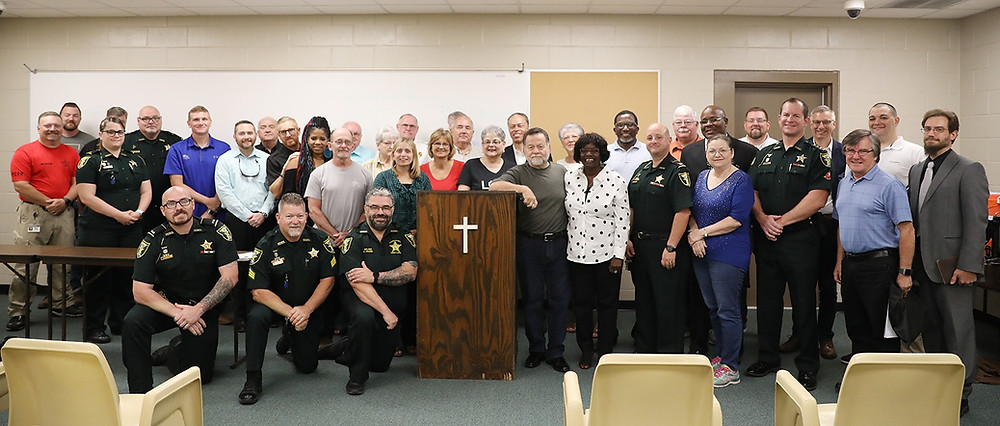 Sheriff Gator DeLoach stands with deputies and local faith leaders in front of room with podium with cross