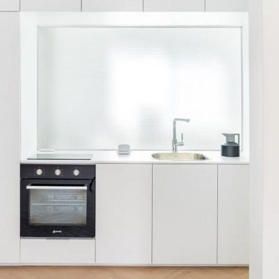 Painel de vidro entre cozinha e banheiro moderniza apartamento