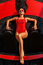 Model in red swimsuit posing on red sports car