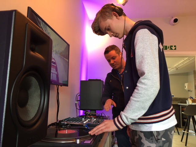 Aduylt showing young person how to mix records for DJing