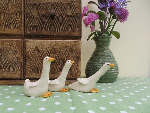 Three white ceramic geese