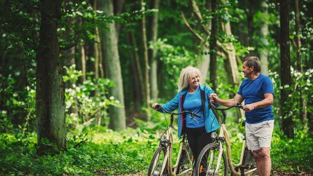 retired-couple-walking-with-bikes-in-the