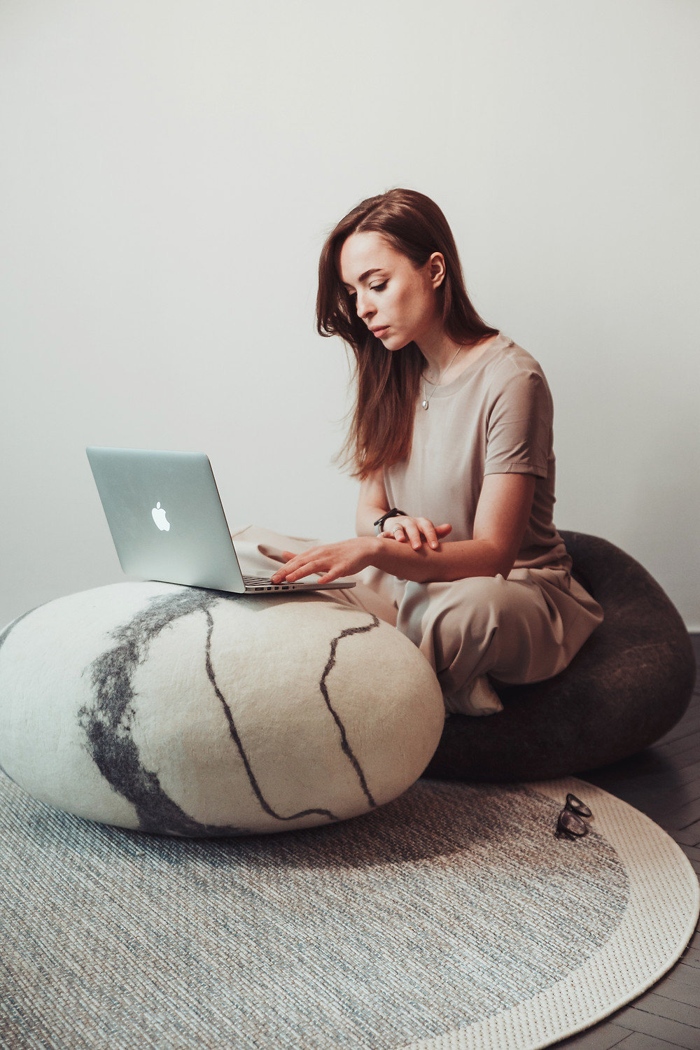 A girl works in a coworking at a laptop. There are interior soft stones by KATSU around her. The stones handmade from natural wool. Woolstones, ottoman rocks. Pouf and pillow handmade from natural wool, look like real stone. Soft interior stones.