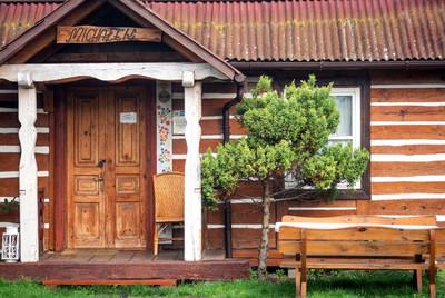 Wejście do drewnianego domu Michałek