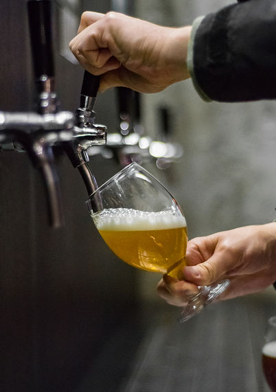 bartender hand at beer tap pouring a dra