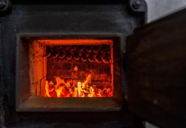 Willi Baumann heizt den großen Ofen an.