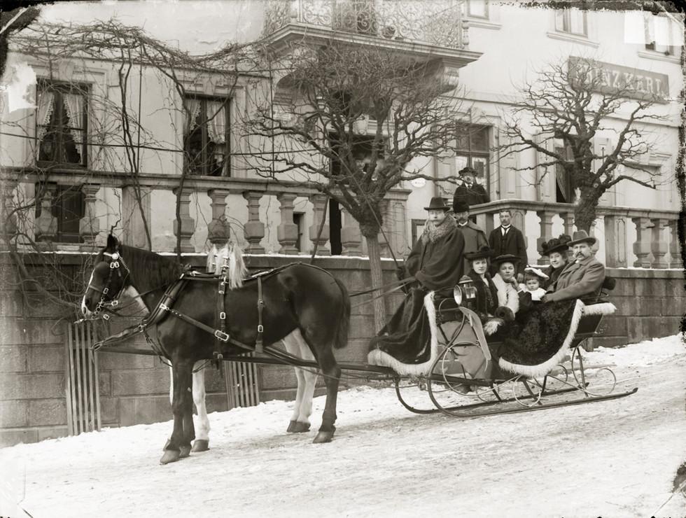 """Ein vollbesetzter Pferdeschlitten vor dem Eingang des """"Prinz Karl"""" in Buchen."""