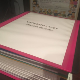 One of many binders documenting the medical journey