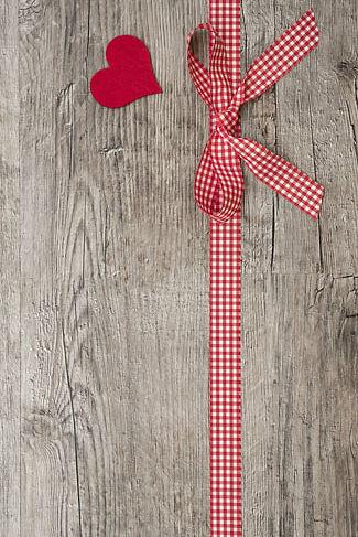 Chèque cadeau, surface en bois avec ruban rouge et blanc et un coeur rouge