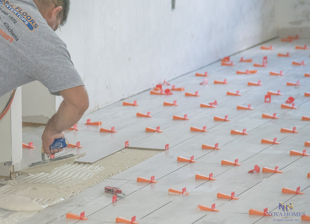 Nova Homes of South Florida installing ceramic tile in a Naples Custom Home Build
