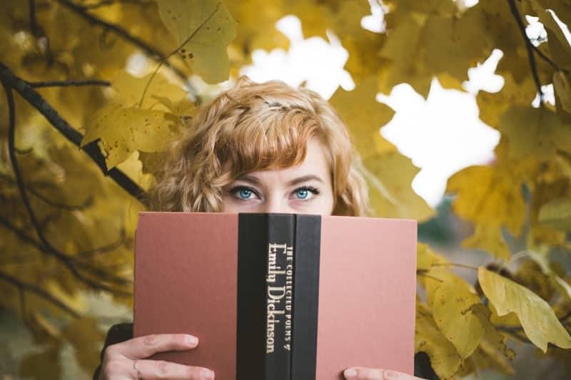Woman peeking over an open book