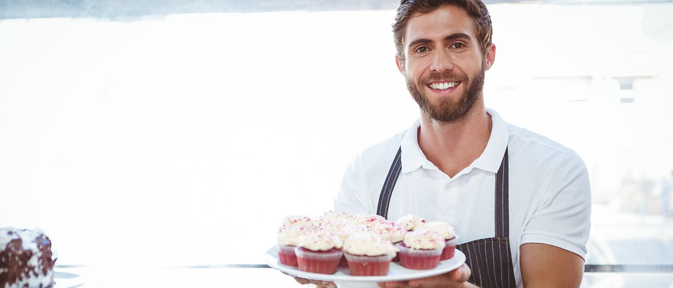 smiling-worker-holding-cupcakes-counter_