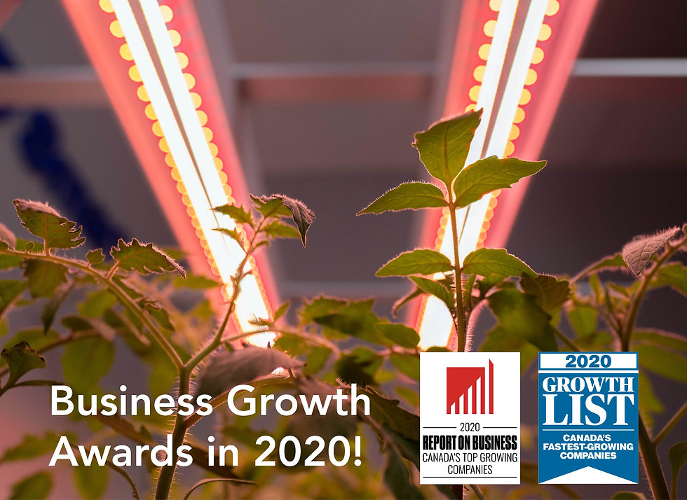 Grow3 led grow light fixtures behind some plants and business growth awards shown