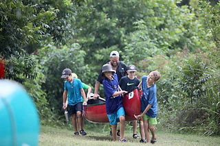 Kids carrying a canoe with the help of their instructor
