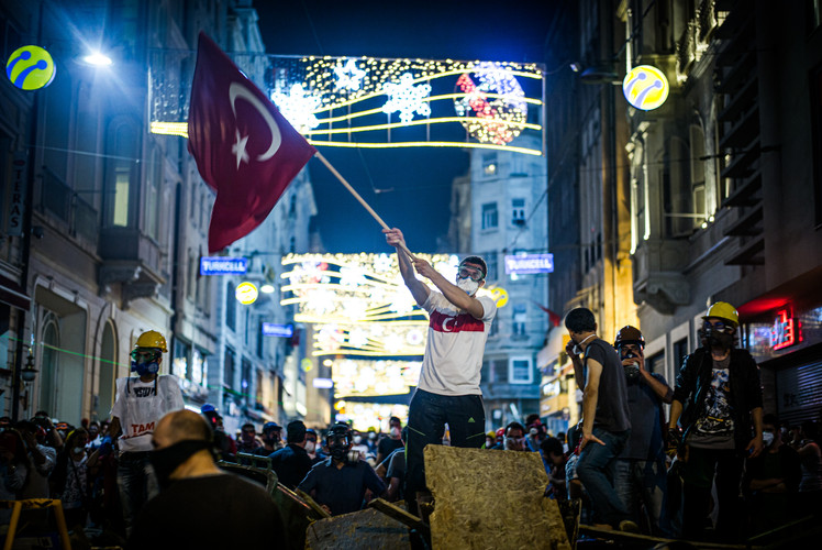 An anti-government protester waving the flag of Turkey while standing on makeshift barricades errected by protesters on İstiklâl Caddesi (Independence Avenue) in Istanbul (Turkey, 2013).