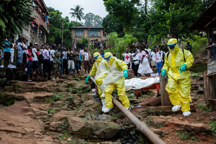 A burial team in a township in Freetown, Sierra Leone carries an Ebola corpse on a stretcher (2014).