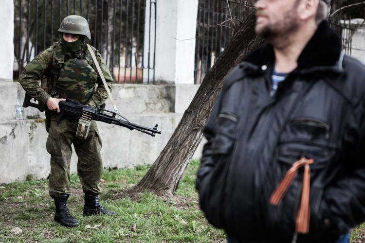 A Russian soldier without any visible insignia armed with a machine gun in front of a military facility (Crimea, 2014).