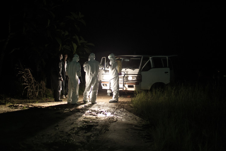 A burial team is preparing for the retrieval of the corpse of an Ebola victim in a remote village in the jungle of Liberia (2014).