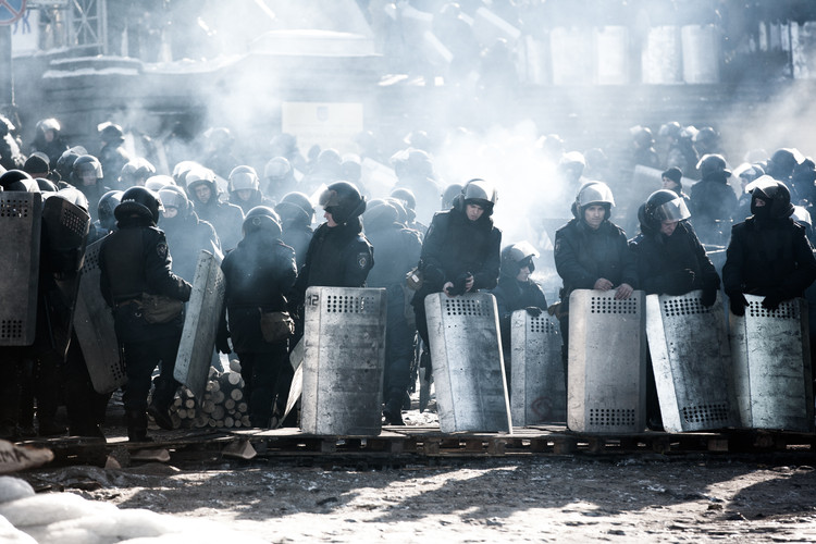 Ukrainian riot police stand guard opposite anti-government protesters during heavy frost in the center of Kiev on January 30, 2014 (Ukraine, 2014).