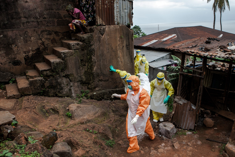 A burial team in a township in Freetown, Sierra Leone picking up deceased Ebola victims while a woman is griefing on top of the stairs (2014).