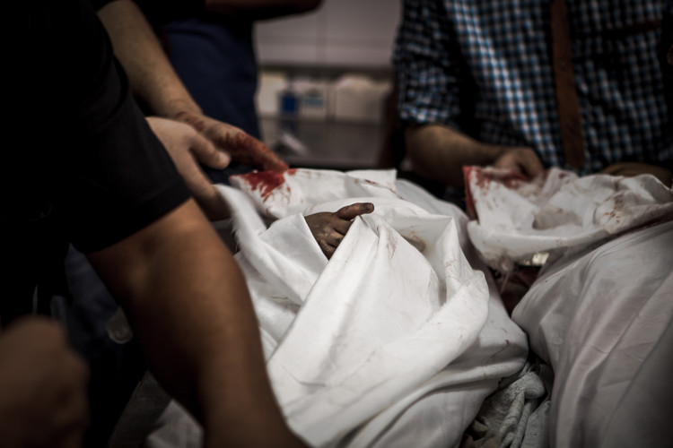 The bodies of two children inside the Gaza City morgue who had died during an airstrike by Israel Defense Forces are being prepared for their burial (Gaza City, 2014).