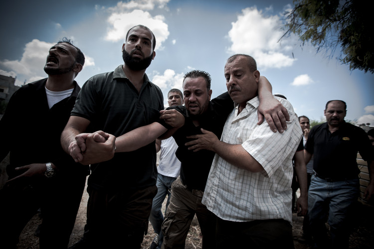 Family members holding up a man during a burial who is mourning the death of his children who had been killed by Israeli airstrikes the day before (Gaza City, 2014).