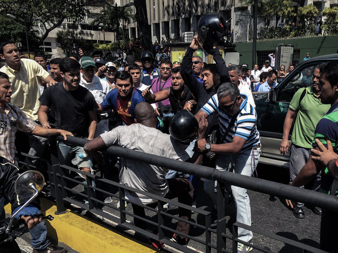 An angry mob attacking an alleged thief on a busy street in downtown Caracas (Venezuela, 2016).