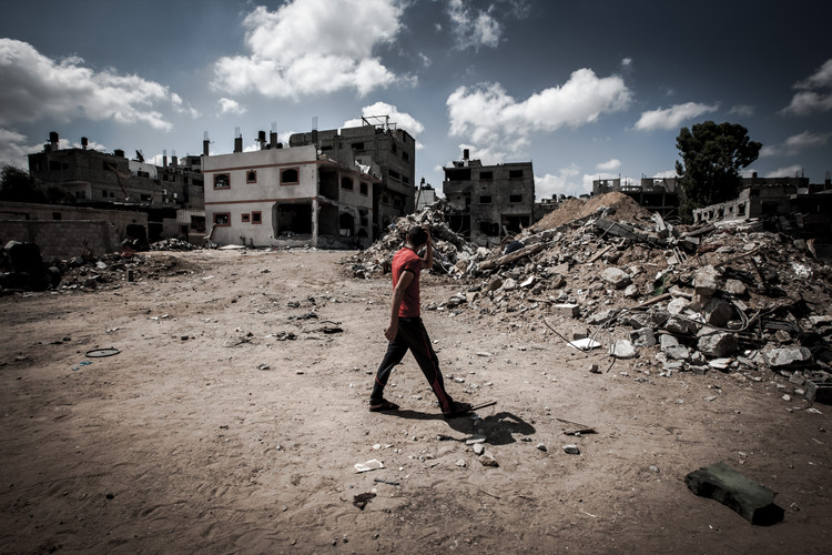 A young man walks by the remains of buildings destroyed by rocket attacks from Israeli military (Gaza, 2014).