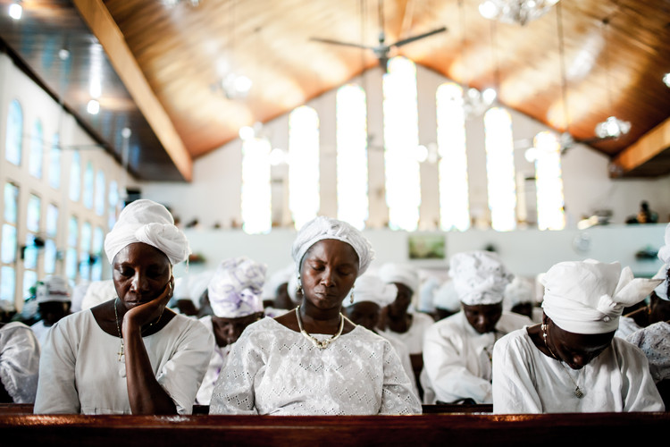Women at a mess in Monrovia, Liberia praying for the end of the Ebola outbreak (2014).