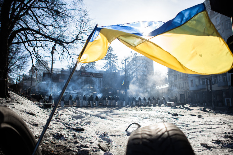 A Ukrainian flag waving on top of barricades built by Anti-government protestors occupying Maidan Square in Kiev (Ukraine, 2014).