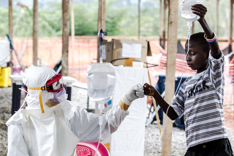 Dr. Alexander Kumar from the British Red Cross giving a fist-bump to a young boy infected with Ebola holding the drip for him (Sierra Leone, 2014).