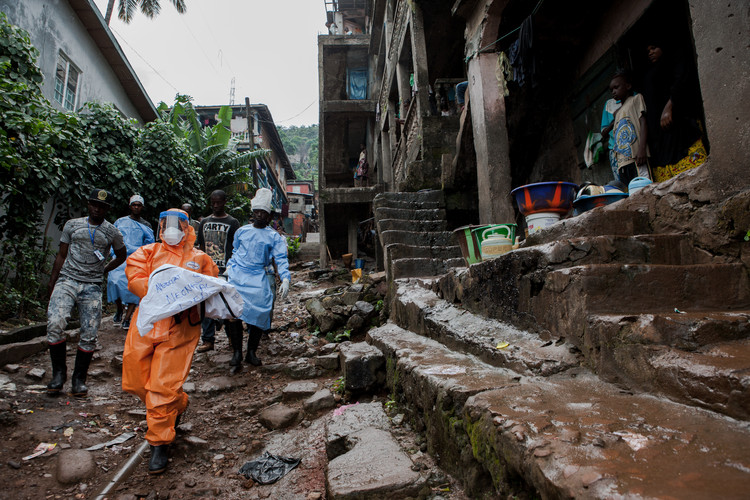 A burial team in a township in Freetown, Sierra Leone carries a body bag containing a dead infant who has died to Ebola (2014).