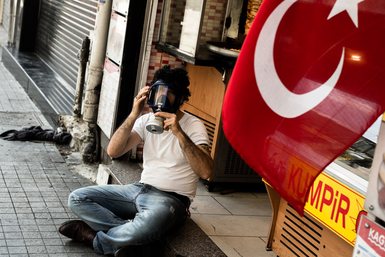 An employee of a bakery on İstiklâl Caddesi (Independence Avenue) in Istanbul is wearing a gas mask to protect himself from high amounts of tear gas fired by Turkish riot police during clashes with anti-government protesters (Turkey, 2013).