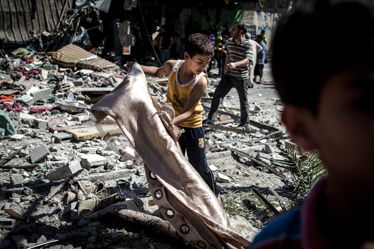 A child searching the debris of a building destroyed by an airstrike from Israeli military during the Gaza war (Gaza City, 2014).
