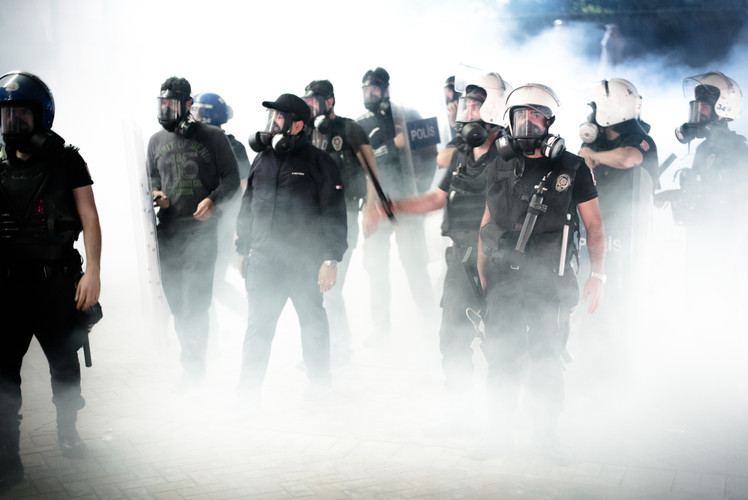 Turkish riot police emerging from clouds of tear gas they have previously fired into the entrance of the Divan Hotel in Istanbul. The hotel functioned as a rally point for anti-government protesters during the Gezi Park unrest (Turkey, 2013).