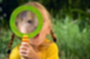 Girl looking through a magnifying glass.