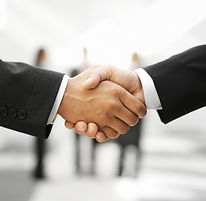 Two men shaking hands and sharing a sales brochure