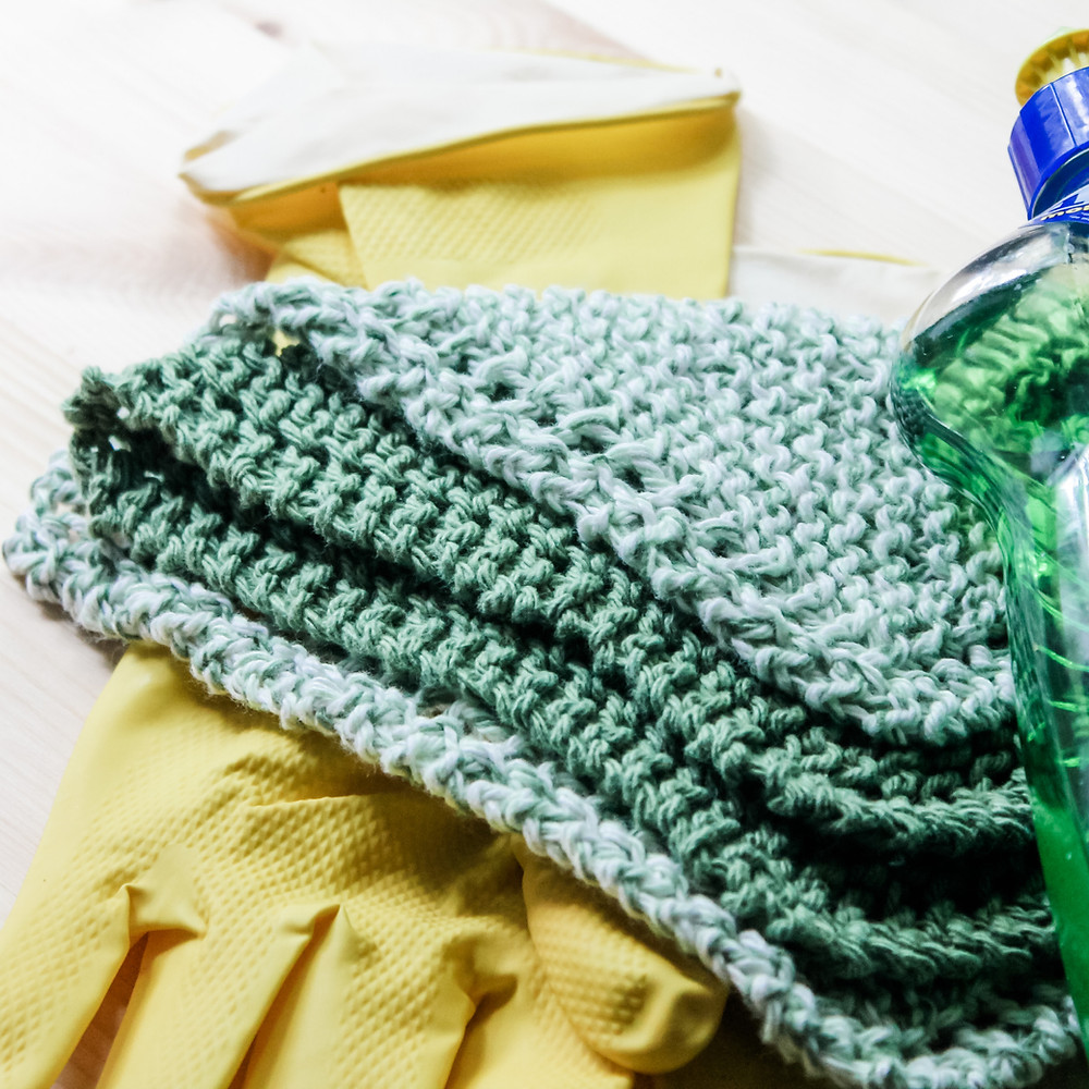 A set of two green cotton knit dish cloths, laying on top of a pair of yellow rubber gloves next to a bottle of green dish soap.