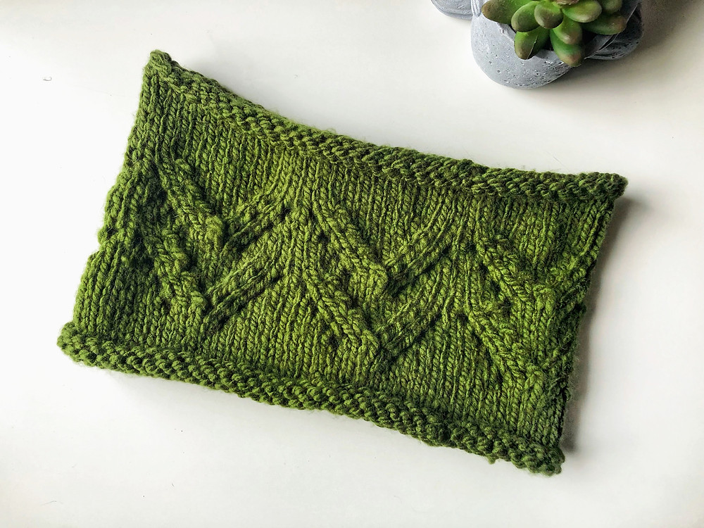 A flat lay of a dark green chunky knit cowl with a pine tree lace detail on a white background.