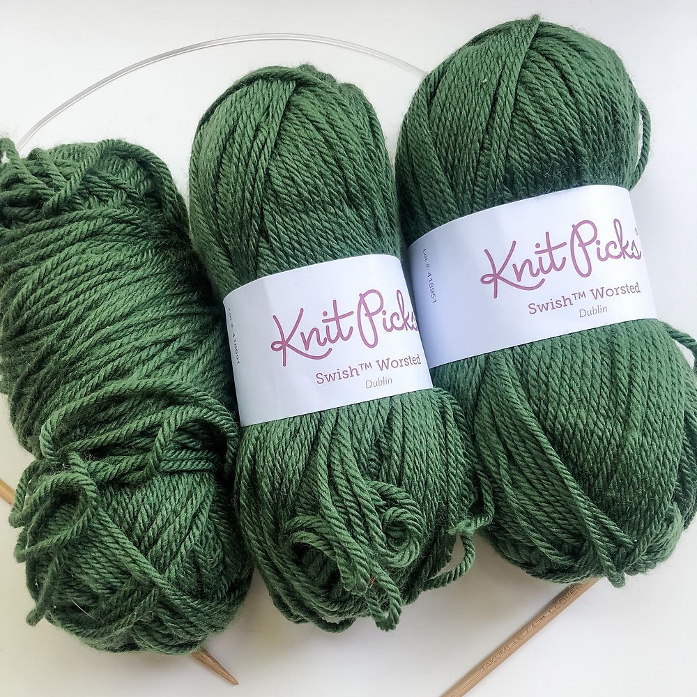 A flat lay of three balls of green yarn on a white background and a set of wooden circular knitting needles. Two balls of yarn have a white label and one has no label.