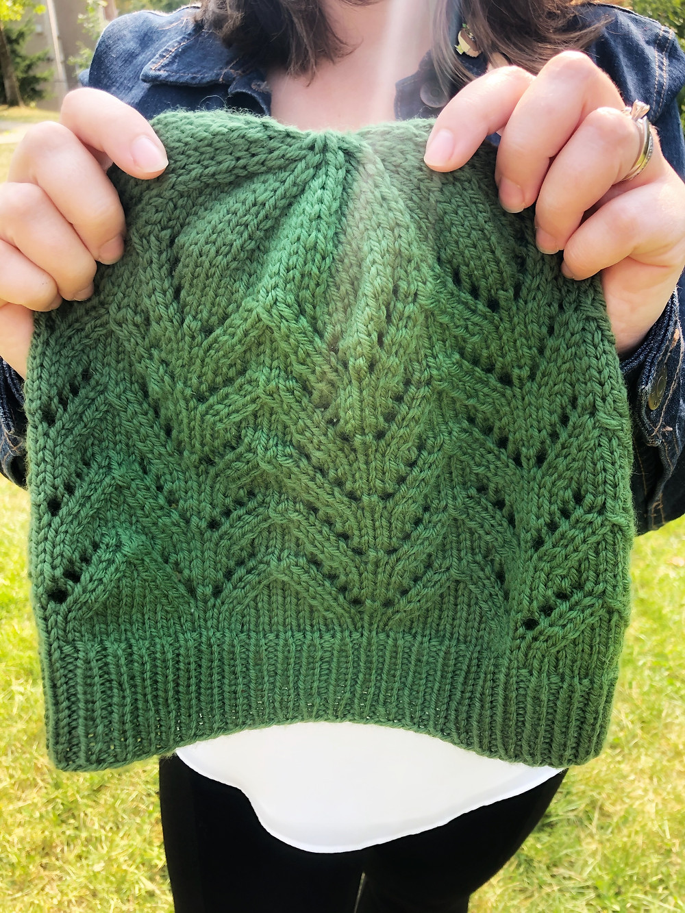A close up of a woman holding a green knit hat with lace stitches in her hands.